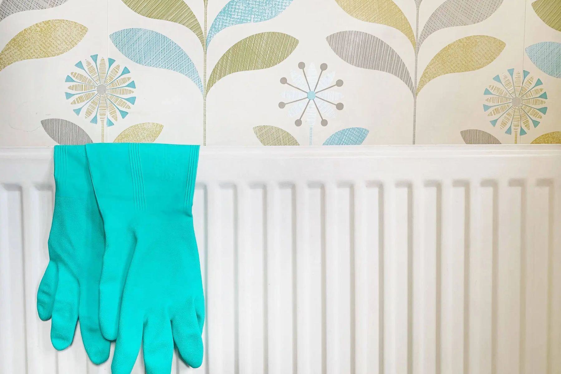 Blue cleaning gloves hanging over white radiator as part of radiator cleaning process