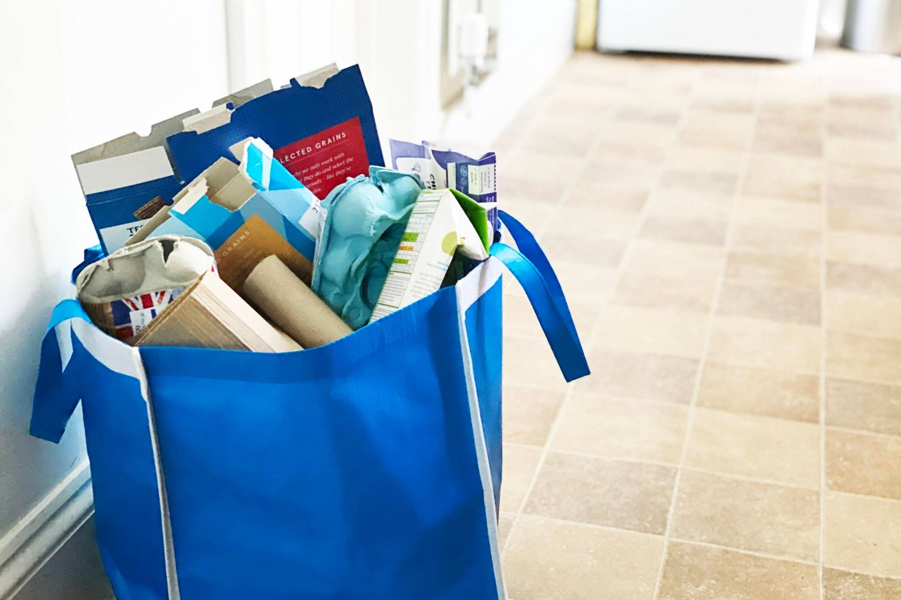 A bag containing a variety of cardboard items, including cereal boxes and egg cartons