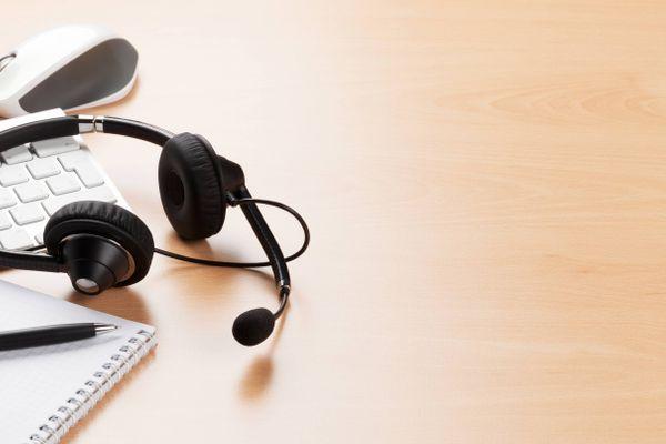 zestaw słuchawkowy, mysz i klawiatura na drewnianym stole