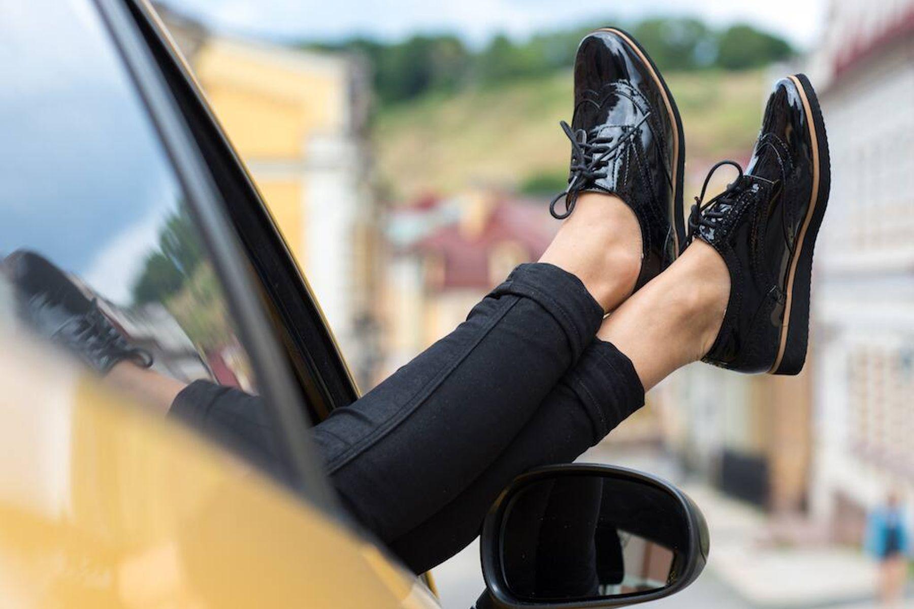seseorang mengenakan sepatu kulit hitam dengan kaki di luar jendela mobil