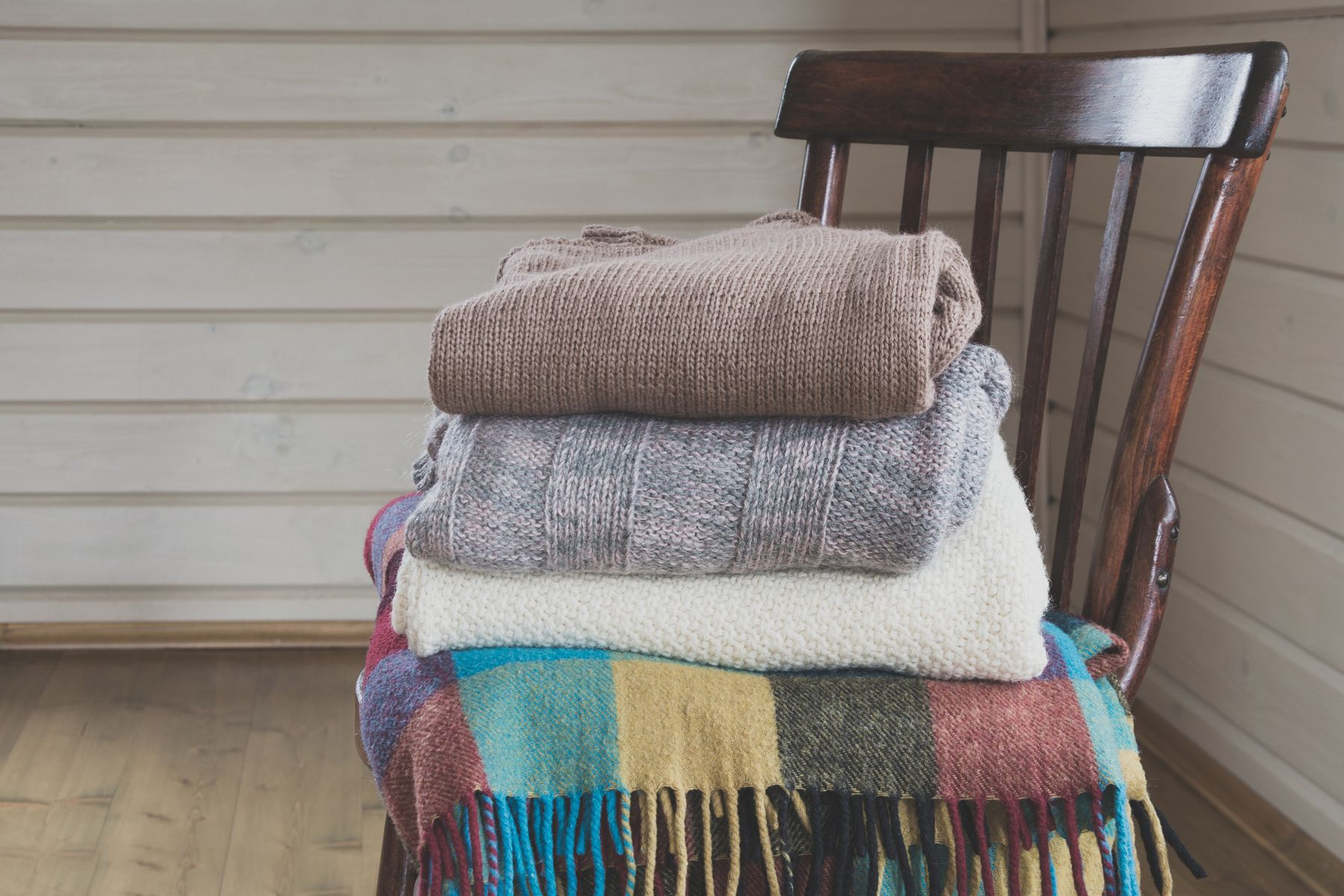 How to wash wool: blankets and jumpers folded in a pile on a chair