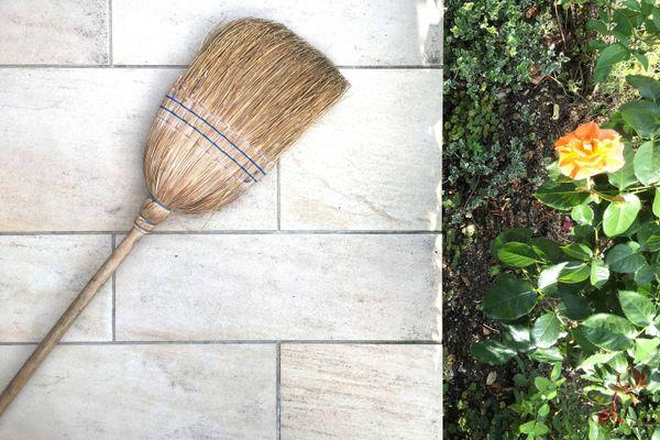 drewniana miotła na podłodze patio obok ukwieconego trawnika