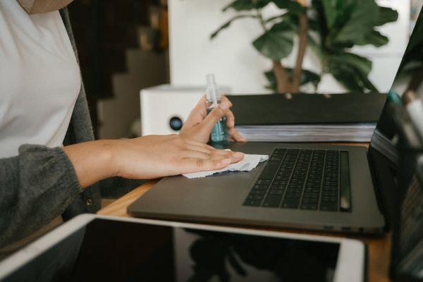 Sprey ve bezle laptop yüzeyini temizleyen biri