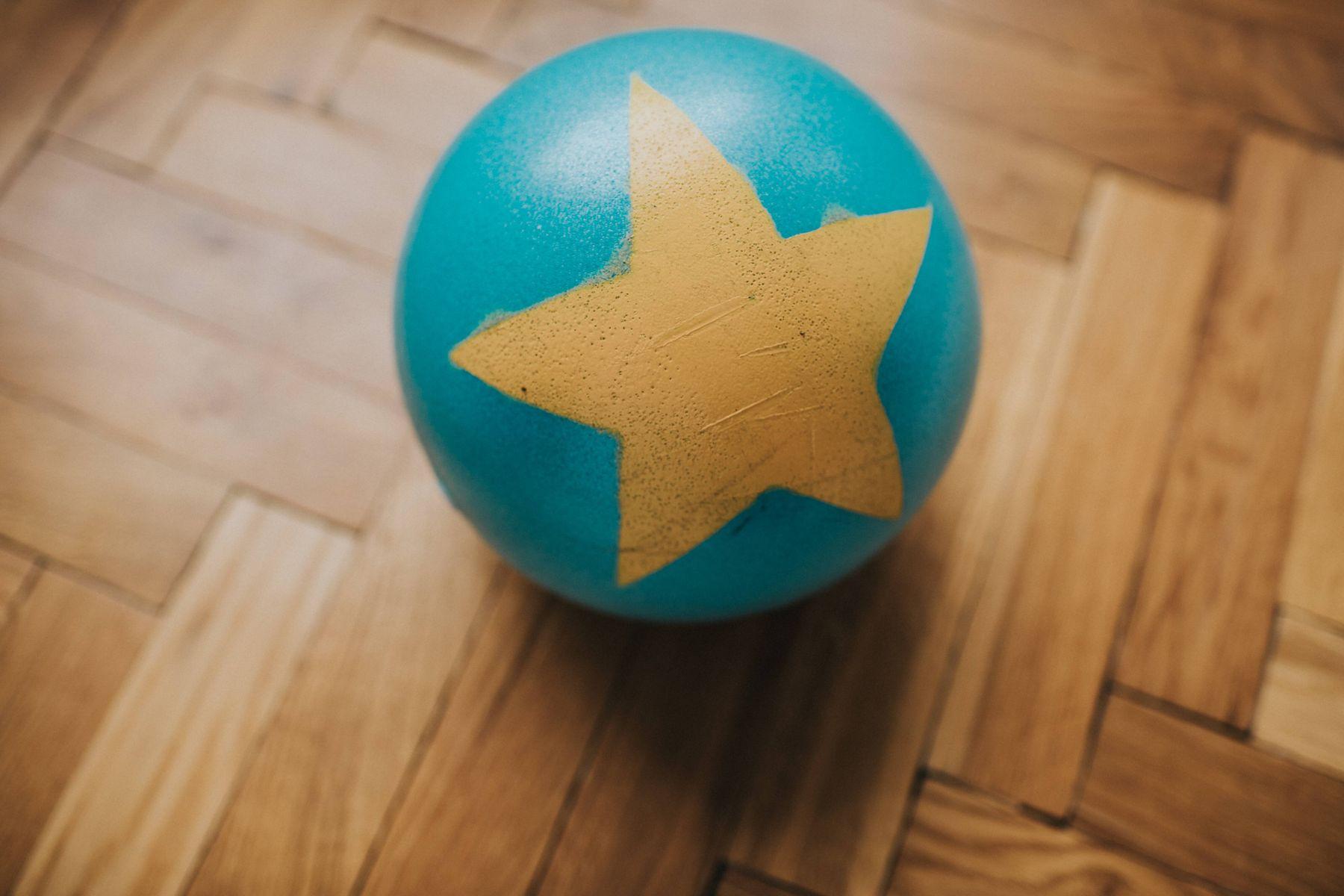 niebieska i żółta piłka na drewnianej podłodze