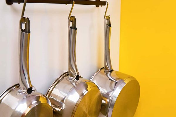 Silver hanging pans against yellow backdrop for 10 tips from a professional pot washer