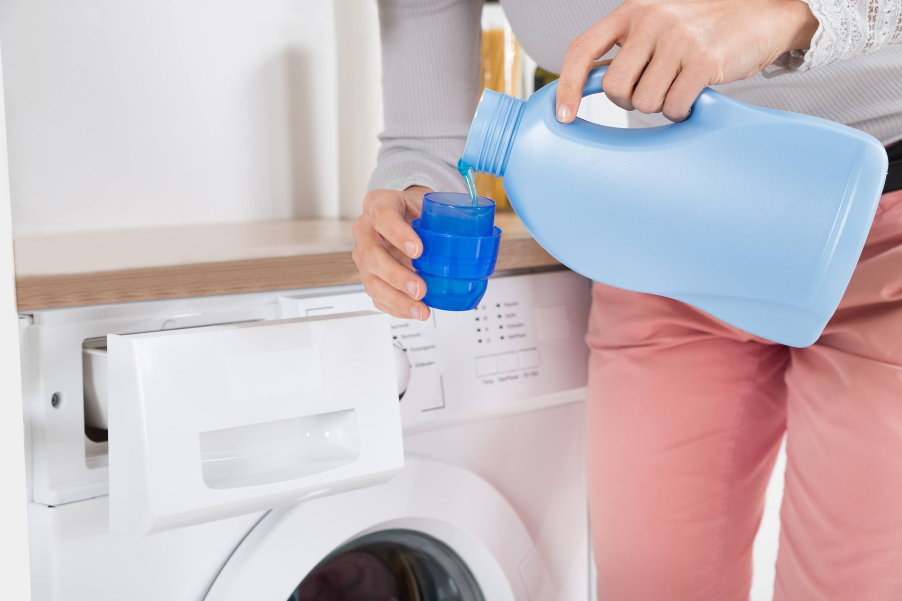 powerful laundry detergent poured by person