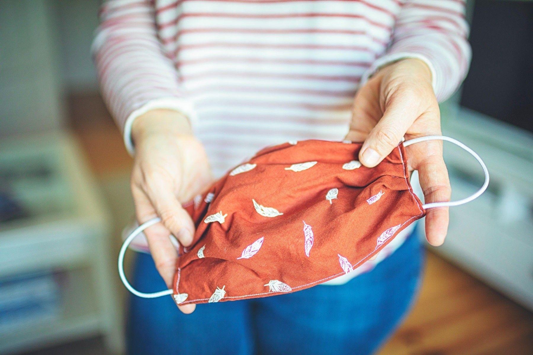 Mãos de mulher seguram uma máscara de pano vermelha
