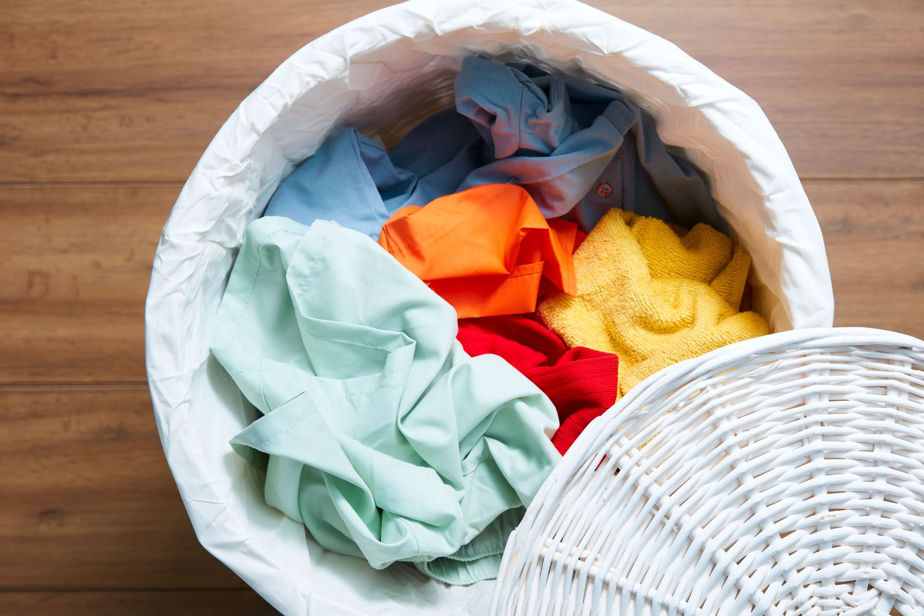 laundry basket filled with coloured fabric and towels