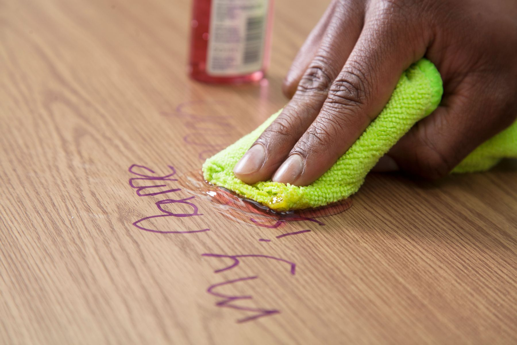 hand scrubbing pen marks to clean wooden surface