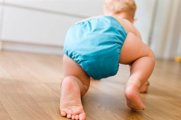 Bebé gatendo con un pañal azul puesto