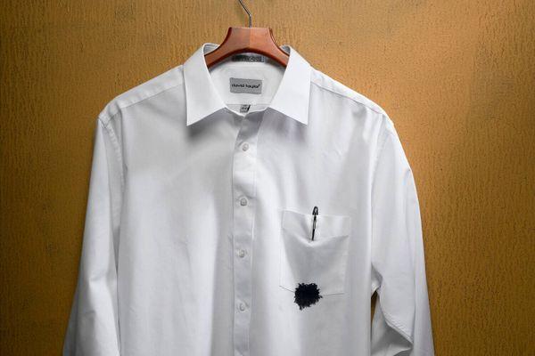 Camisa branca com bolso sujo de tinta preta de caneta