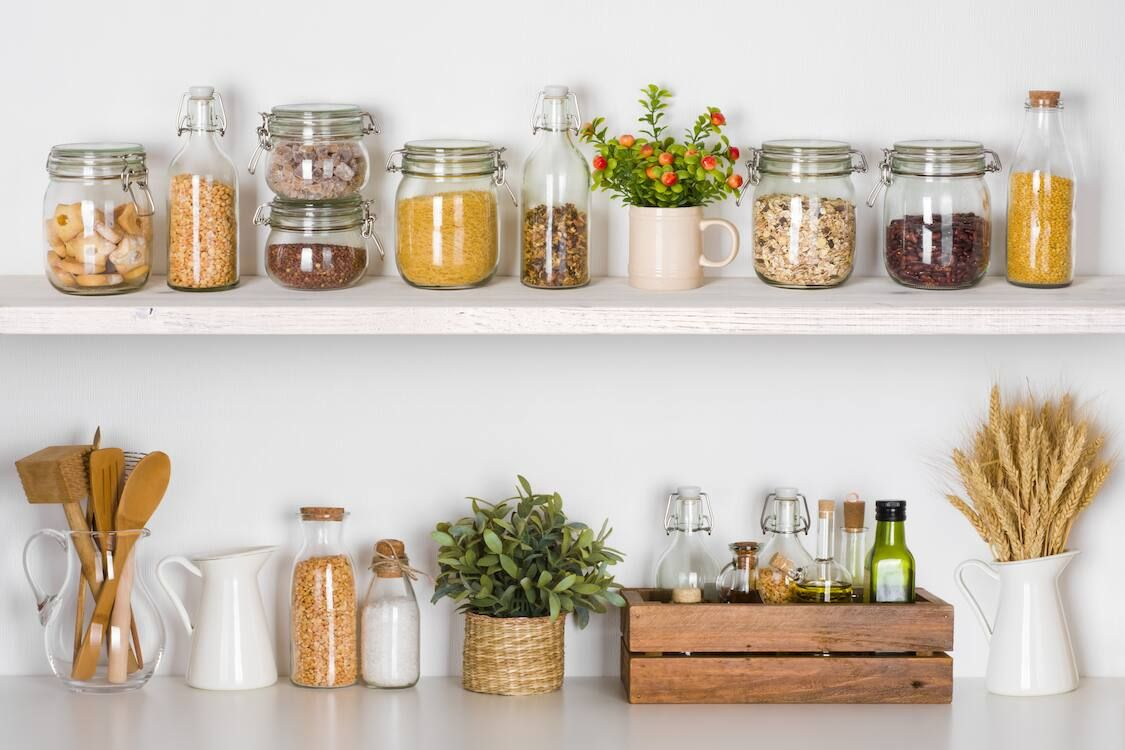 kitchen cabinet with white shelves full of tins and jars of dry food