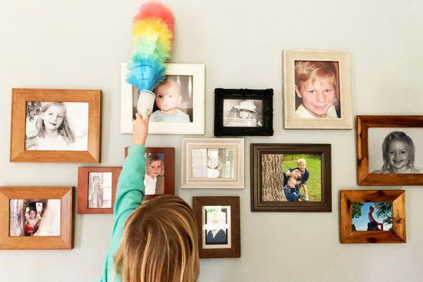 Criança tira o pó de quadros na parede