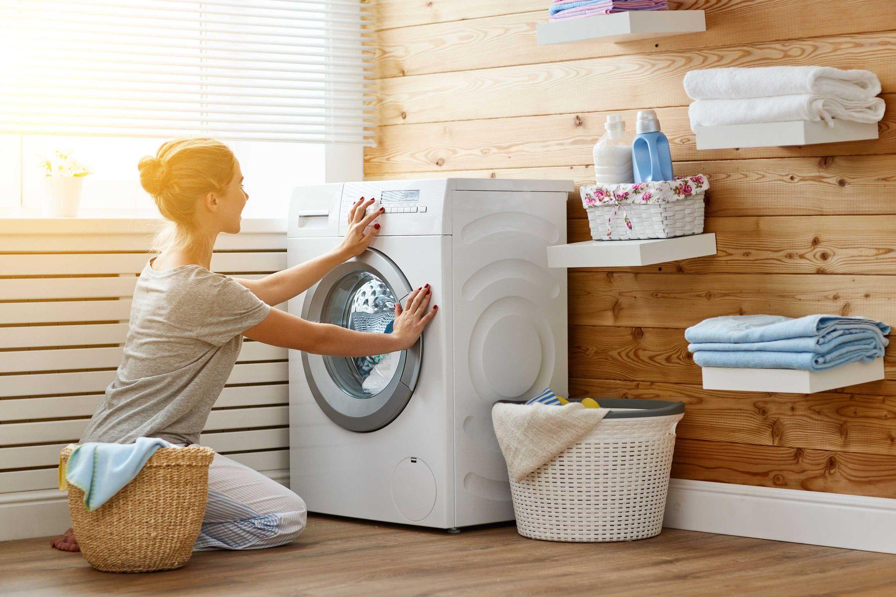 Mulher em uma lavanderia com prateleira de produtos de limpeza