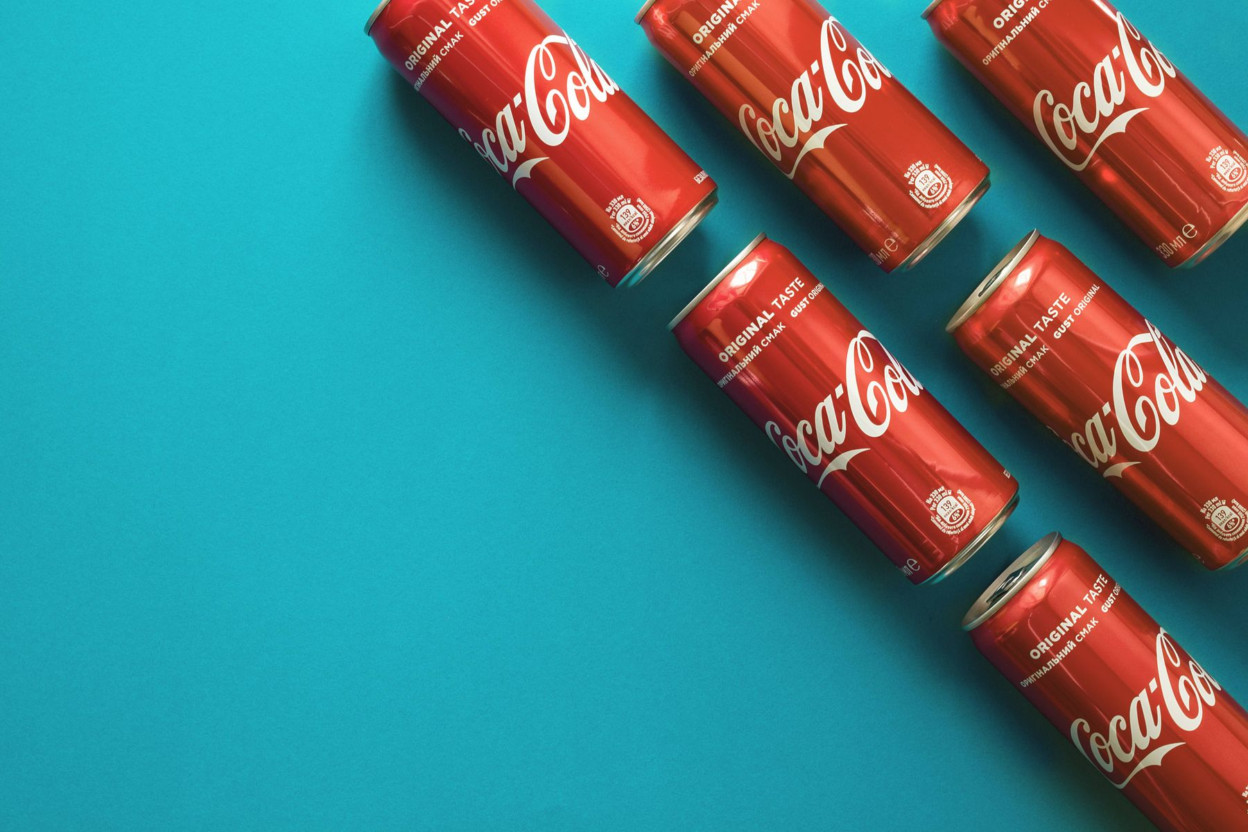 Coca cola cans on blue background