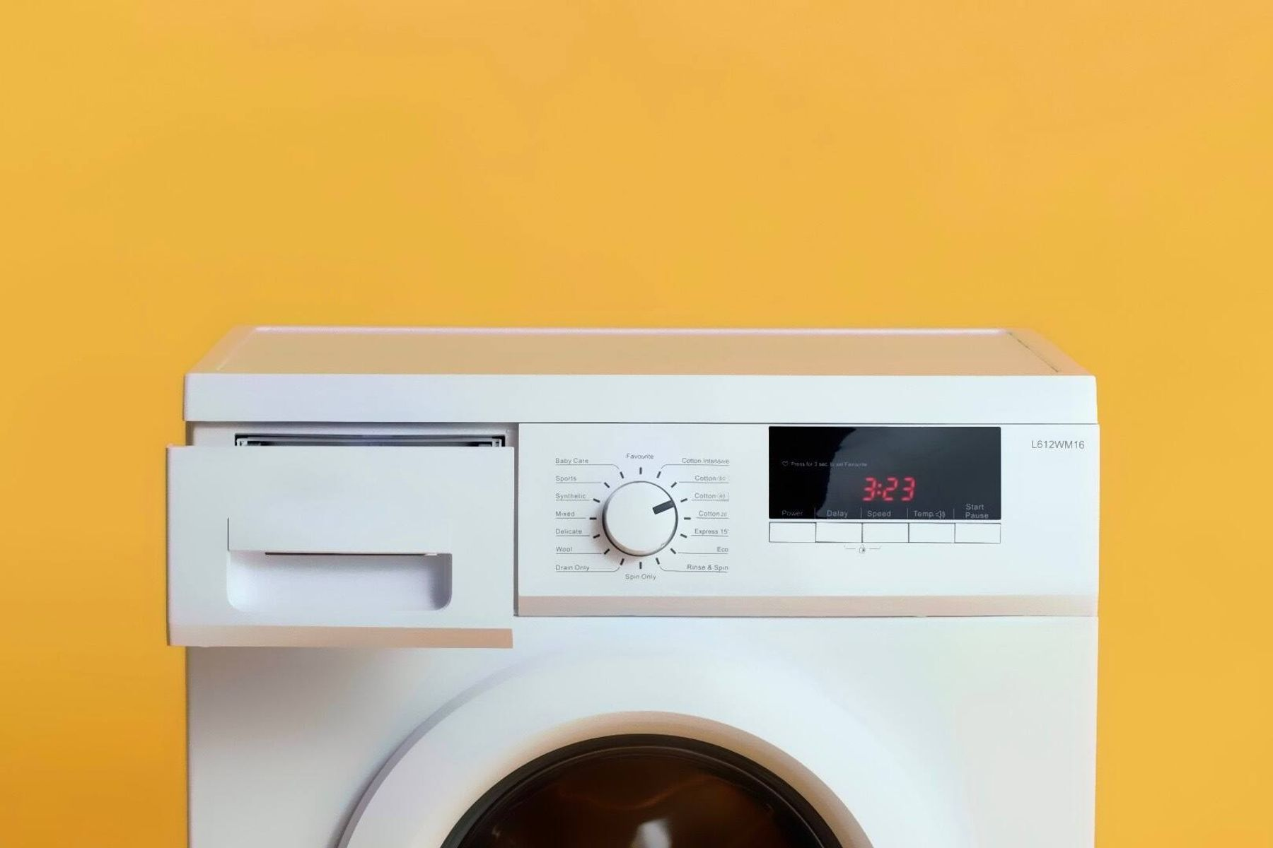 a white washing machine in front of a yellow wall