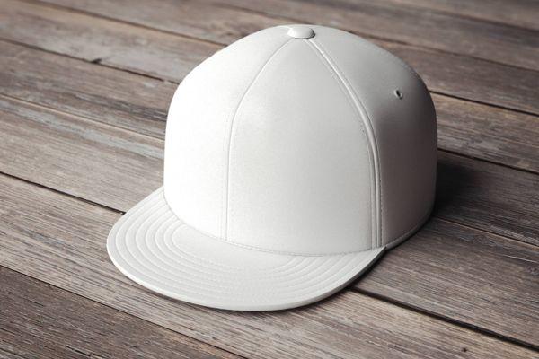 Boné branco em cima de superfície de madeira
