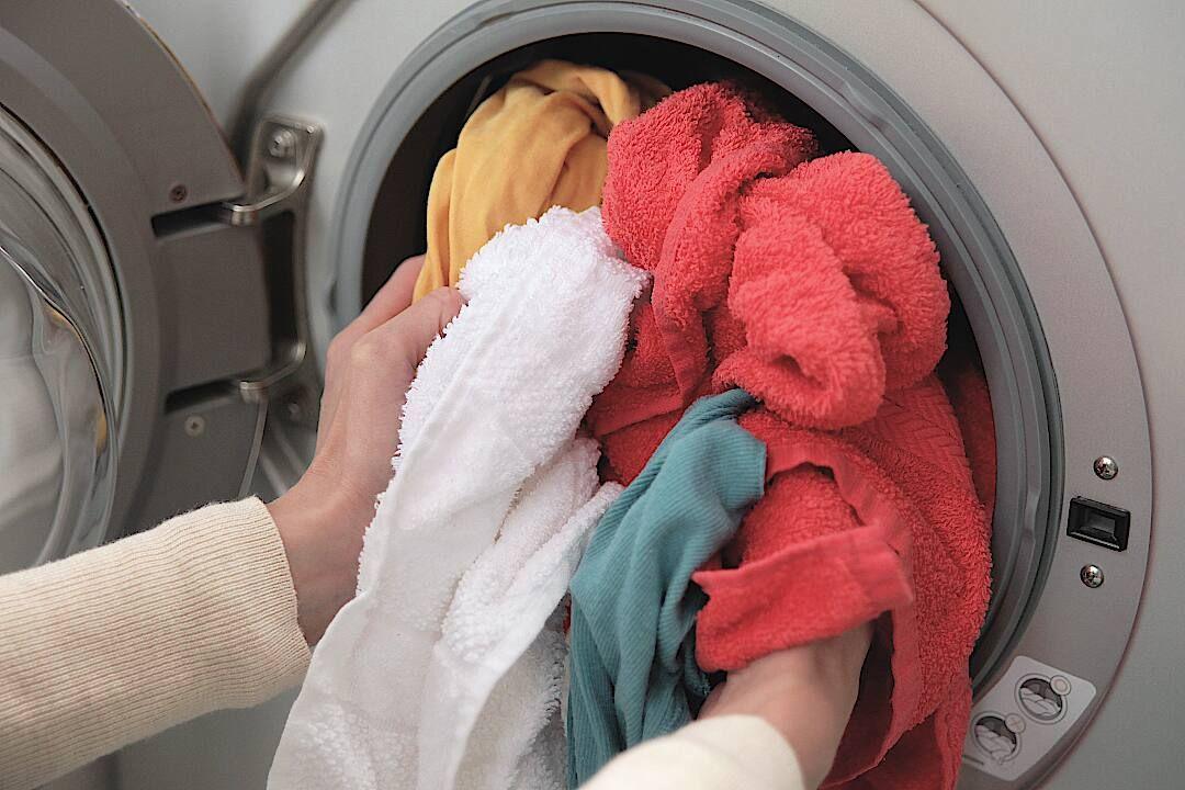 Pessoa colocando roupas para serem lavadas e higienizadas na máquina de lavar roupas