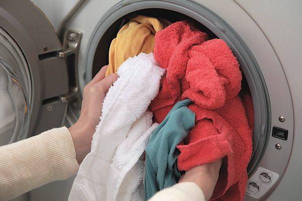Roupas sendo colocadas para lavar na máquina de lavar roupas