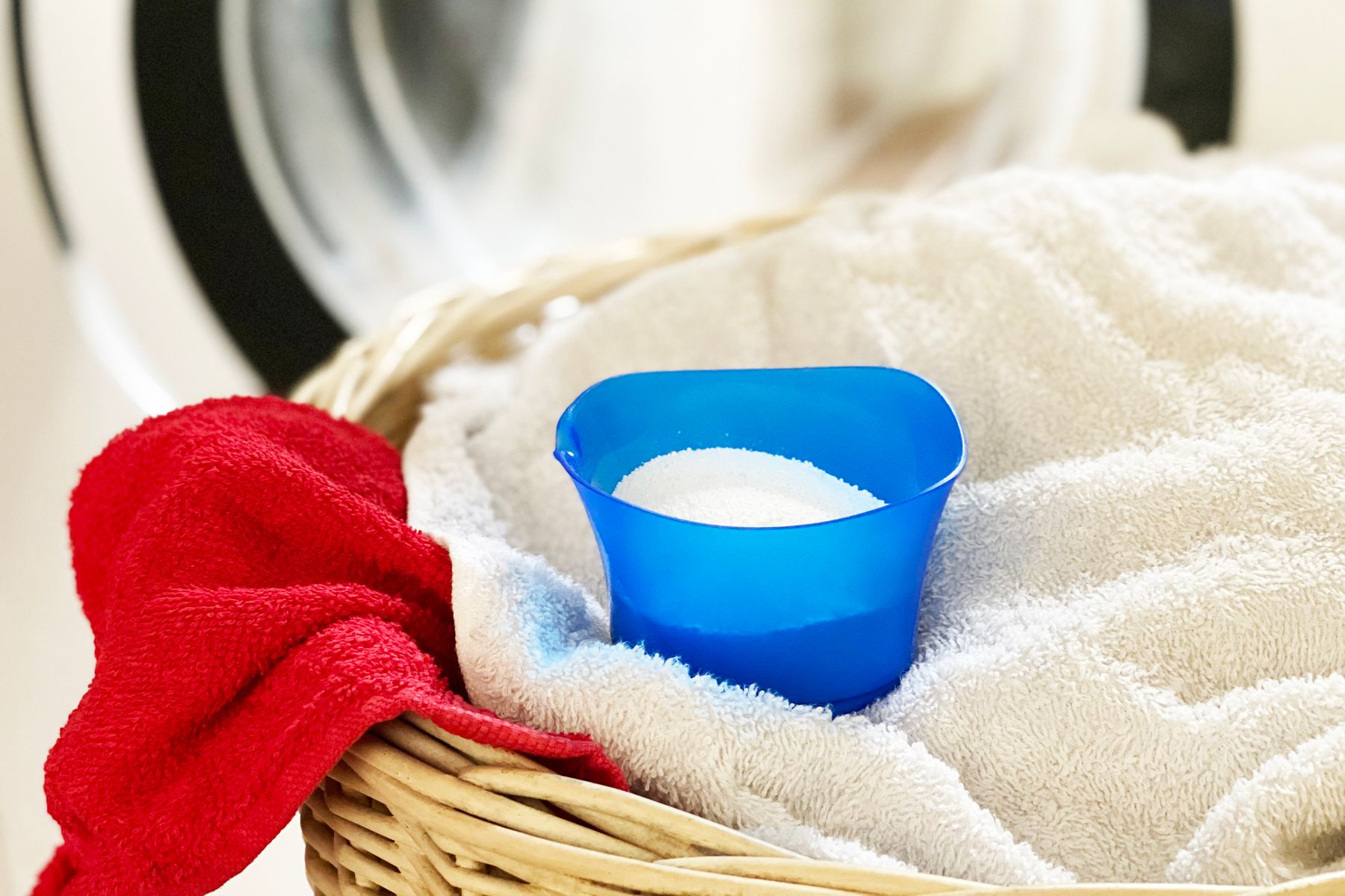 Laundry powder on top of  a basket containing towels