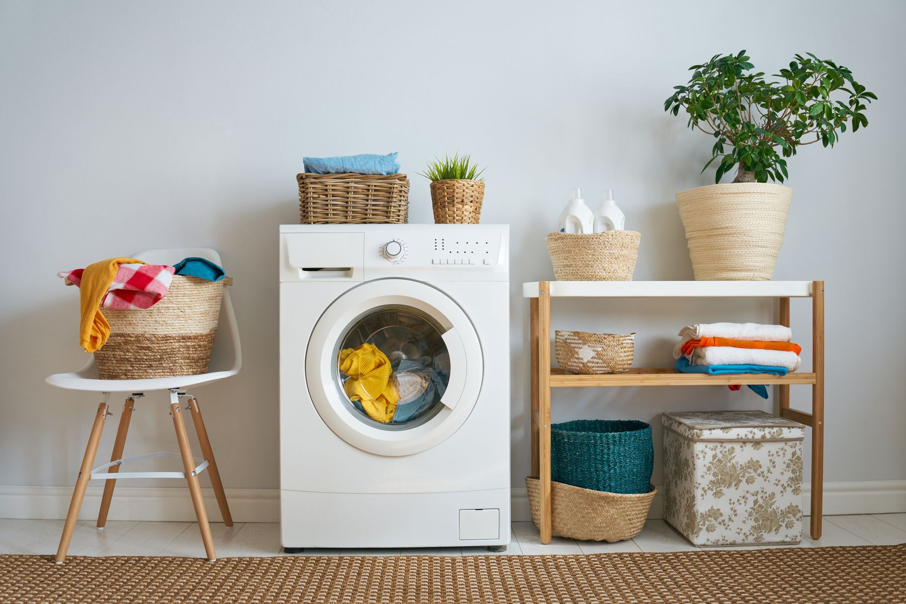 washing machine between chair with bright laundry on top and sideboard