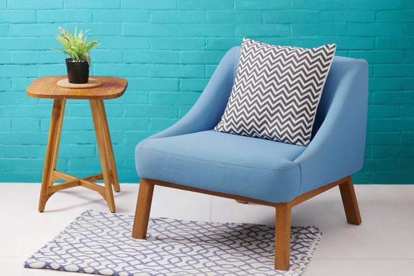Sillón de azul con cojín y mesa pequeña de madera con planta