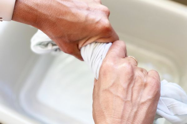 Mãos torcem um pano de prato no balde