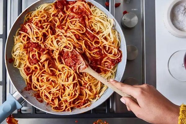 Ocakta bol domates soslu spagetti tavasını karıştıran biri
