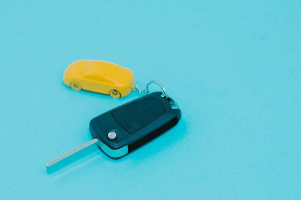 Autoschlüssel mit gelbem autoförmigen Schlüsselbund