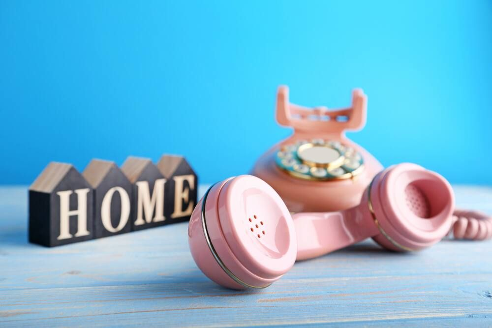 Pink old-fashioned telephone off the hook and small ornament on blue desk