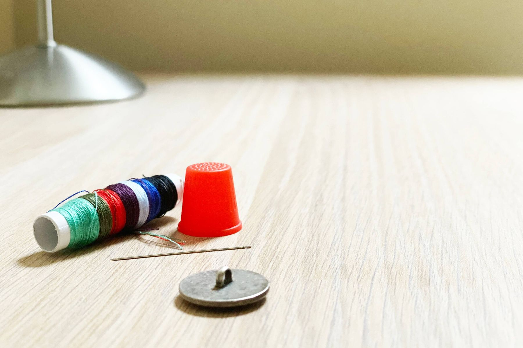 A shank button, with a needle, spool of thread and thimble in the background