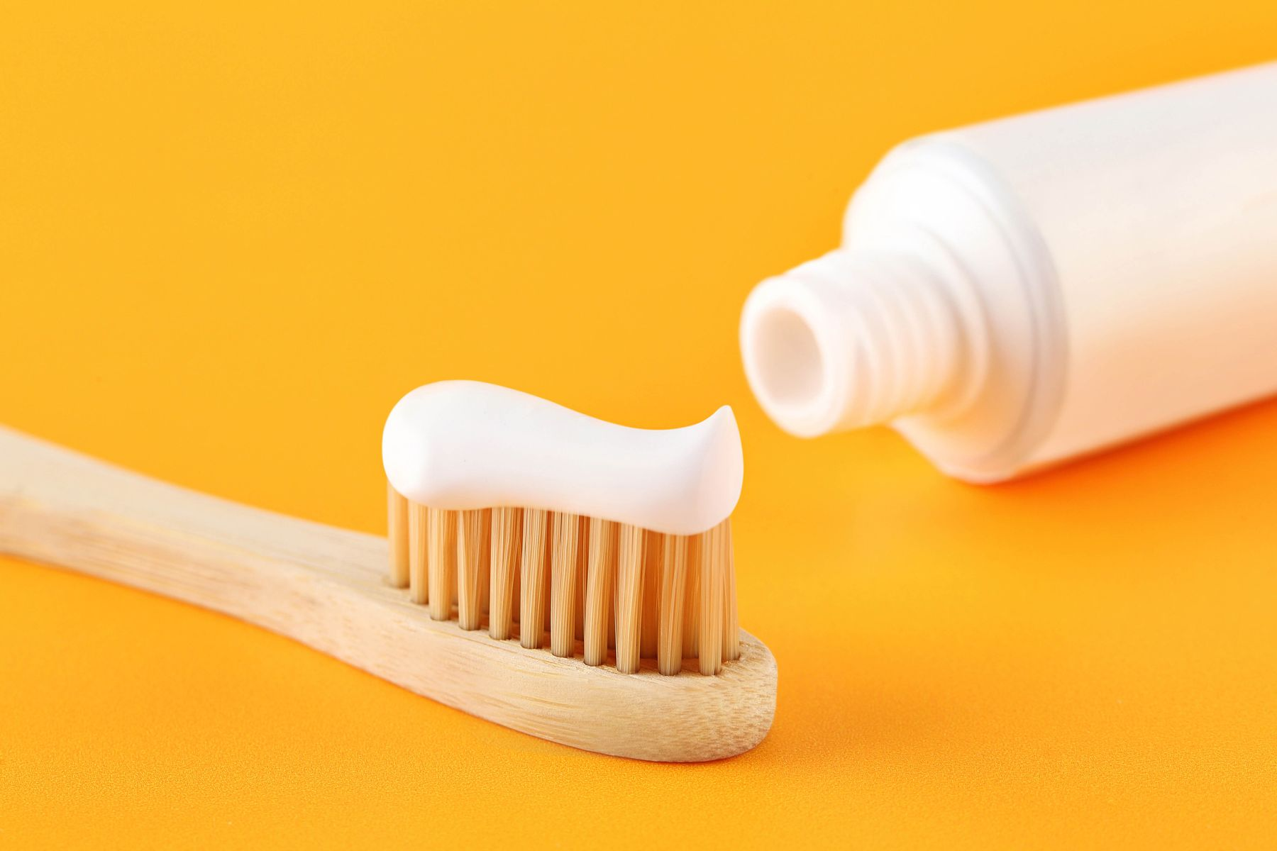 bamboo toothbrush with toothpaste on the top, toothpaste tube in the background