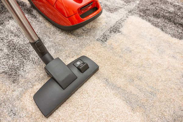 Red vacuum cleaner on carpet after cleaning hoover filter