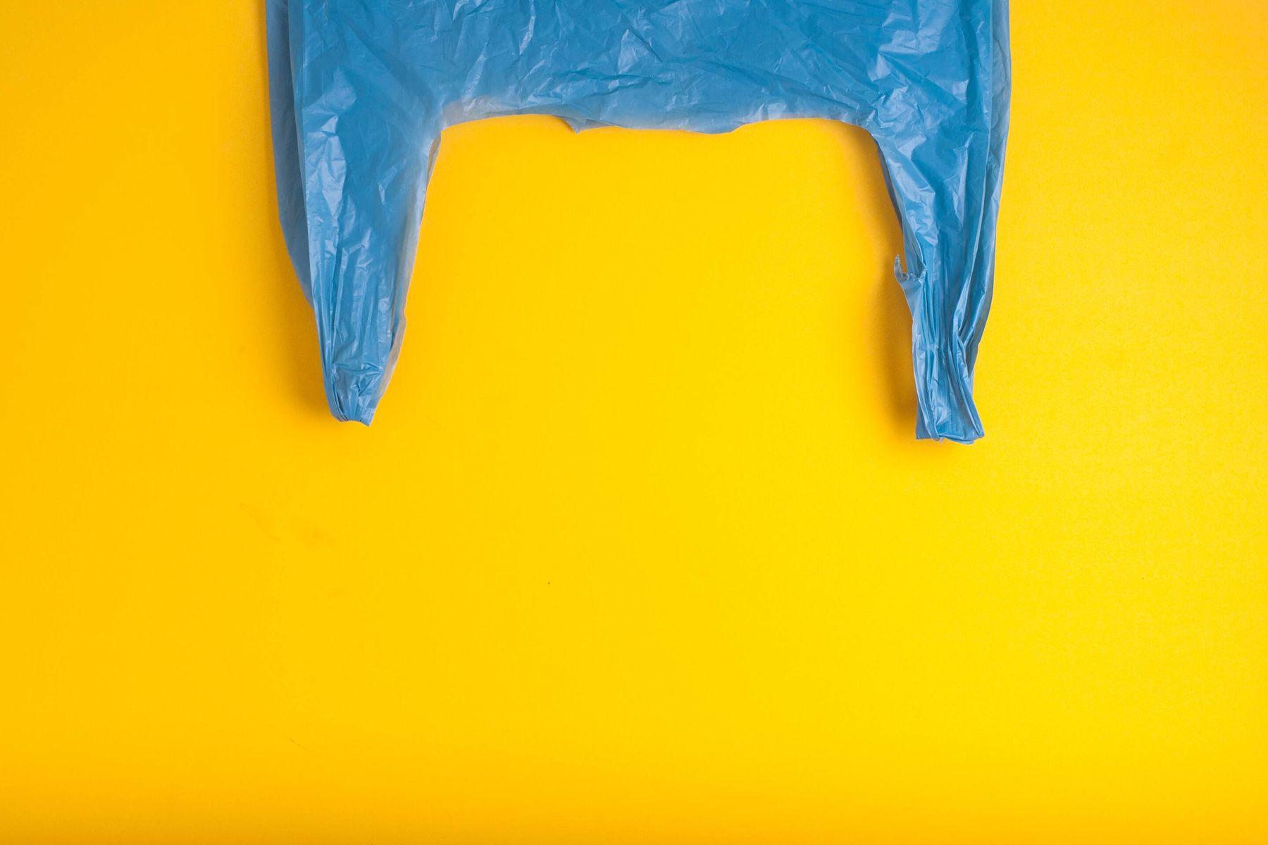 niebieska plastikowa torba na żółtym tle