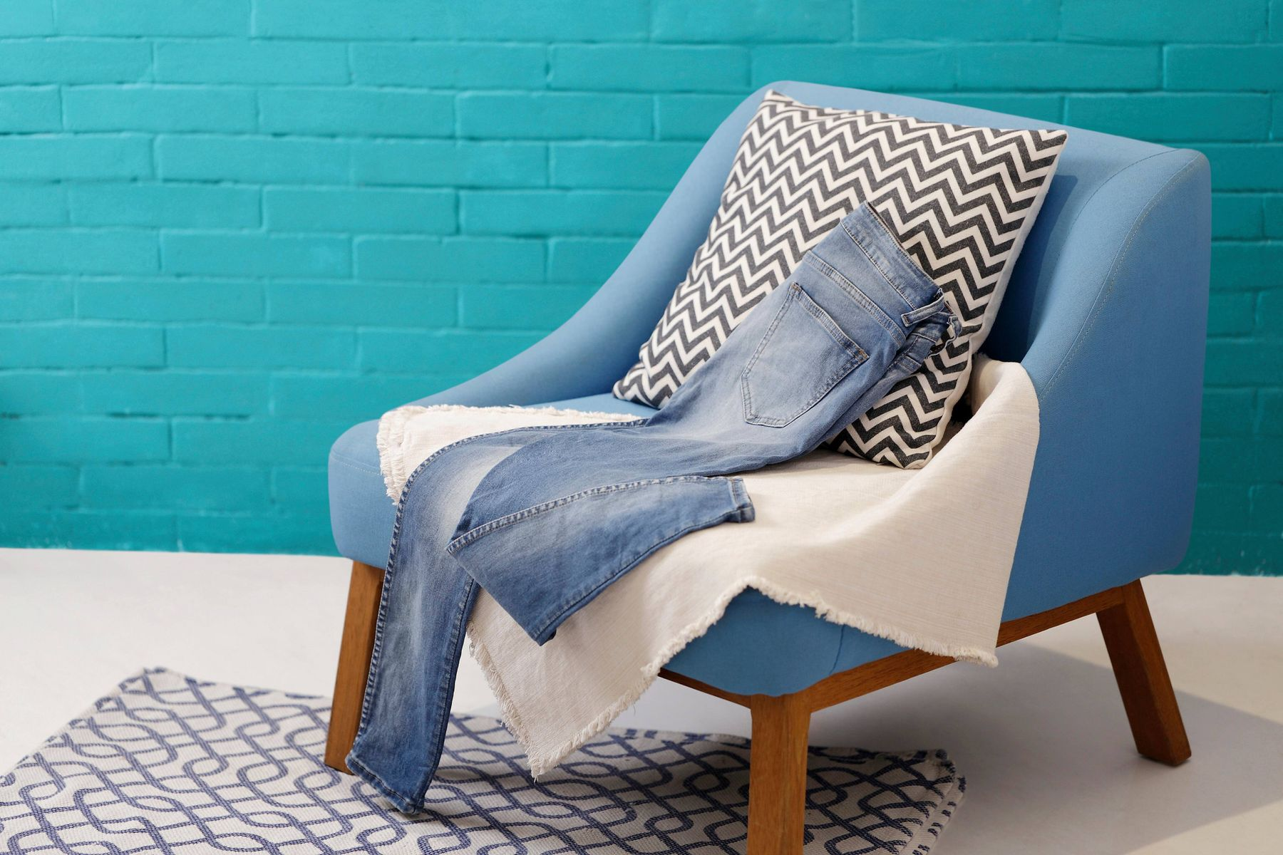 a blue chair with blankets and a pair of jeans