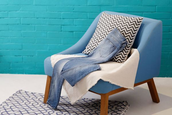 a bluechair with blankets and a pair of jeans