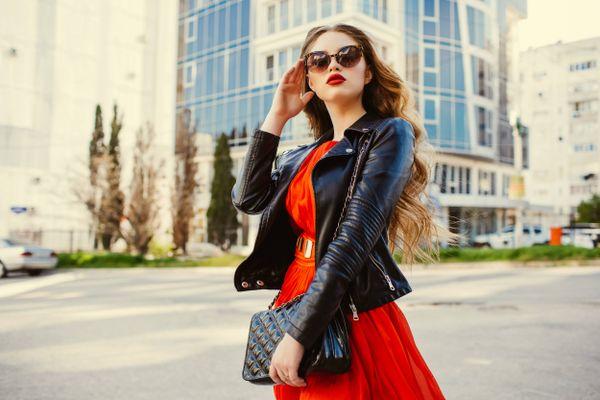 Mulher com vestido de seda vermelho e jaqueta de couro preta