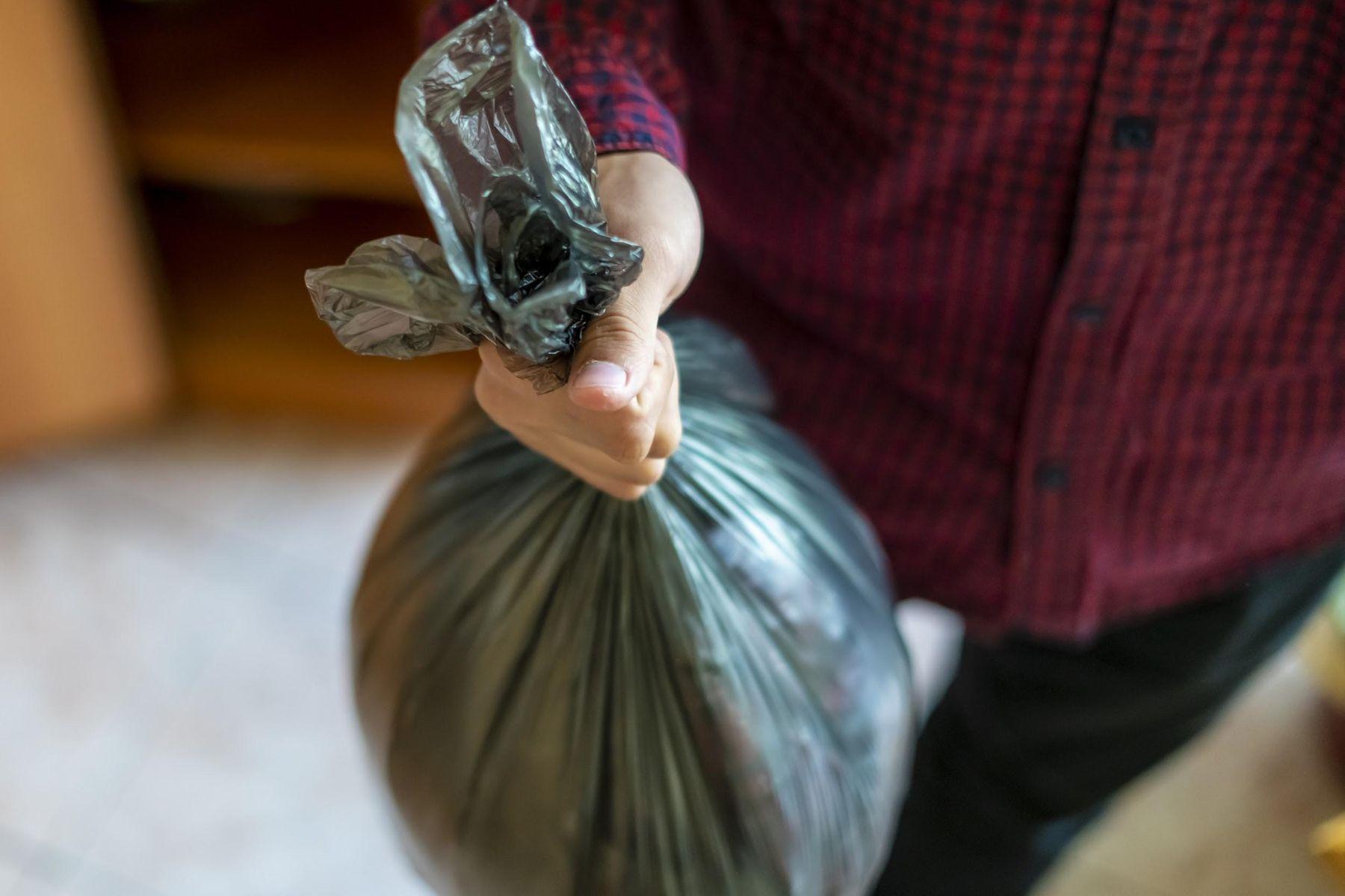 Homem segurando um saco de lixo fechado