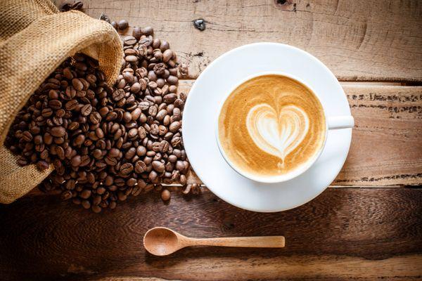 Secangkir cappuccino dan biji-biji kopi