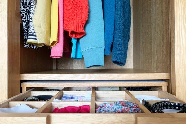 Porta de um armário aberta e uma gaveta aberta, onde se vê várias peças diferentes de roupas, de várias cores.