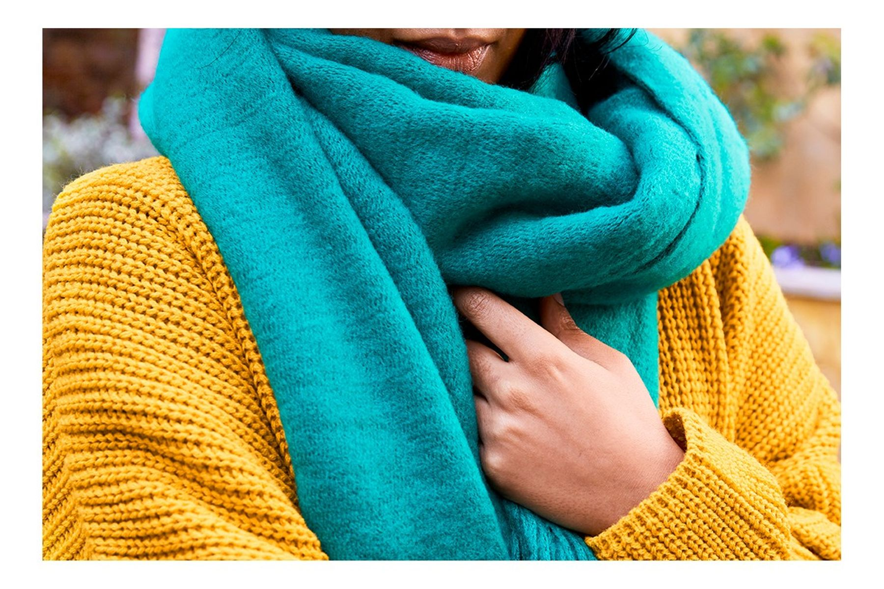 Woman wearing a blue woollen scarf and a yellow jumper after washing wool scarf