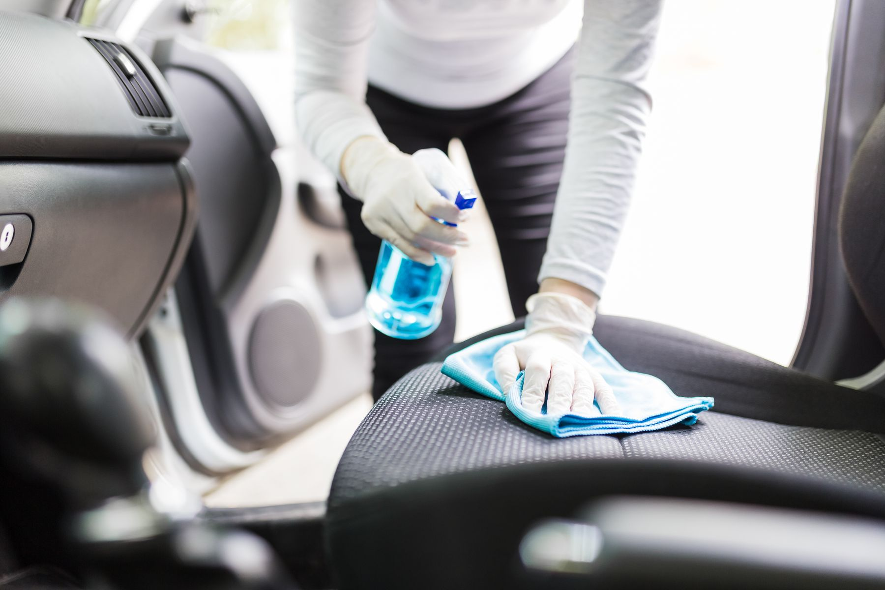 person in gloves cleaning grey car seats with a spray bottle and a cloth