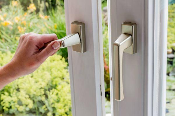 close em mão abrindo porta de vidro com fundo para jardim