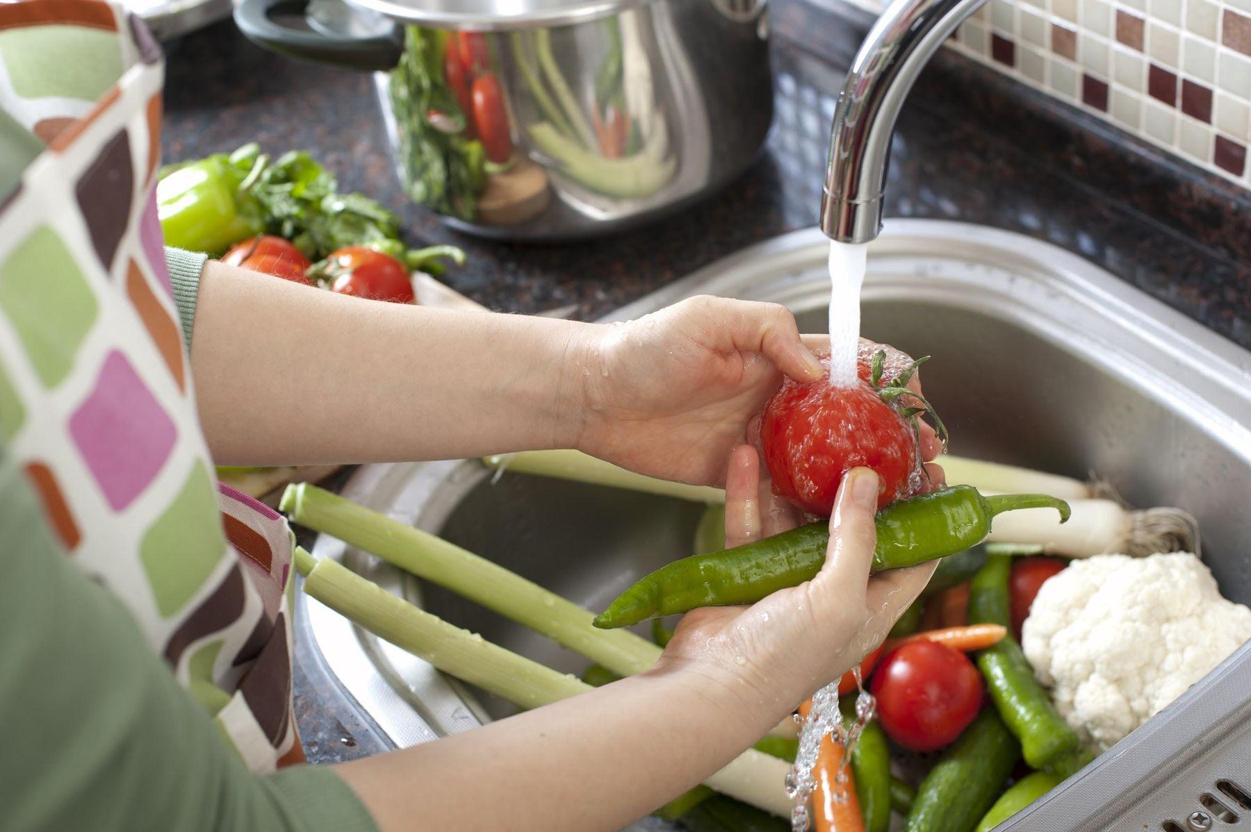 Mulher lavando verduras e legumes em água corrente