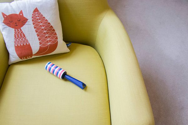 żółty fotel, wzorzysta poduszka dla kota i środki do usuwania włosów