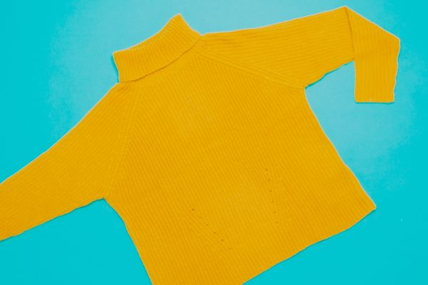 Lint on clothes: Yellow fluffy jumper on a blue background