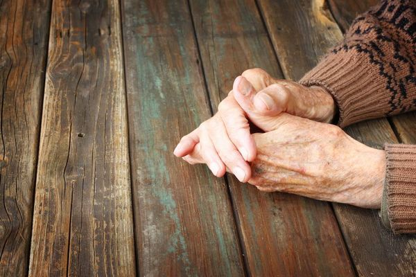 Ageing hands on wooden table top to show characteristics of mature skin