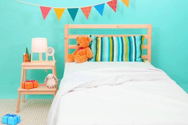 quarto infantil colorido organizado com um urso de pelúcia em cima da cama