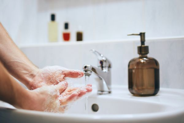 person washing hands with antibacterial soap