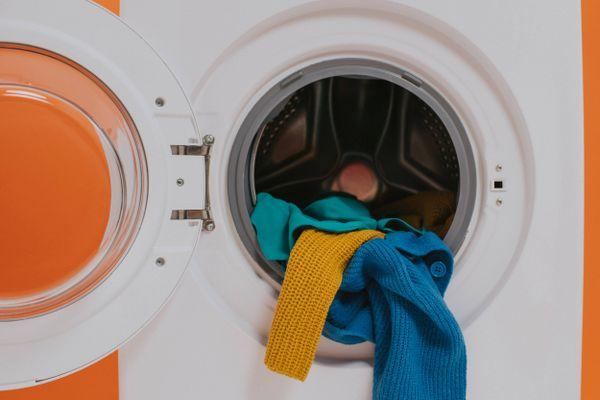 Máquina de lavar com abertura frontal com a porta aberta com roupas coloridas
